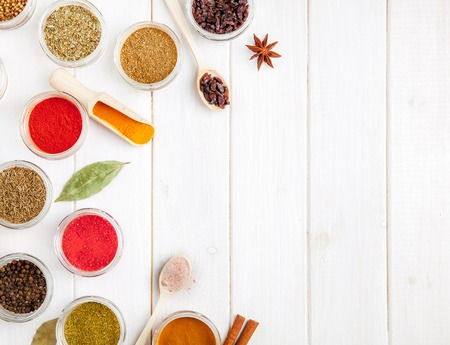 variability: Spices on white wooden background.