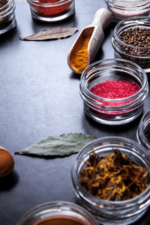 variability: Spices on black background in special jars.