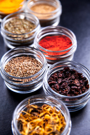 barberries: Spices on black background in special jars.
