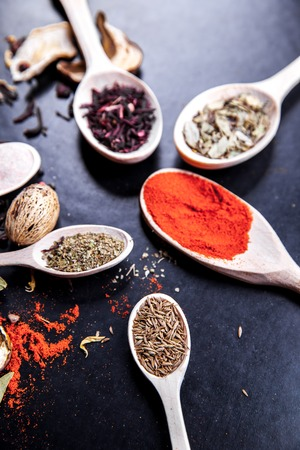 variability: spice in wood spoon on a black background. food Stock Photo