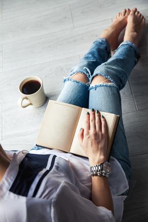 Moderne meisje in gescheurde jeans het lezen van een boek met een grote kop koffie. Mode, lifestyle, lifestyle, recreatie, onderwijs, hobby's. Stockfoto