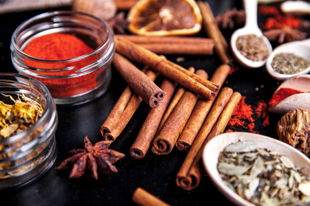 variability: wooden spoons with spices on black background Stock Photo