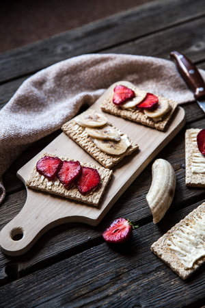 bread and butter: Fruity toast on wooden background. Strawberries, bread, butter and cheese. Stock Photo