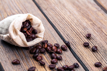 winnower: Coffee beans on the wooden background. Stock Photo