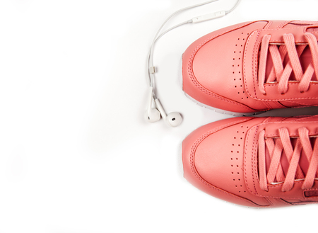 Sporting pink sneakers on a white background with earphones.