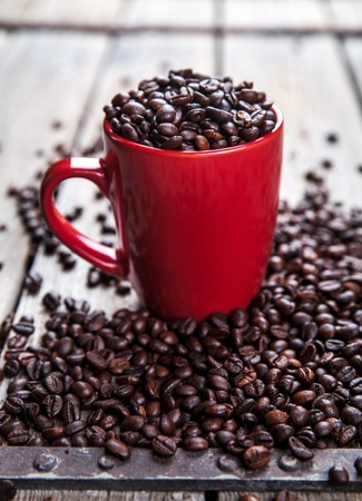 Coffee beans and red coffee cup on wooden background. Drink