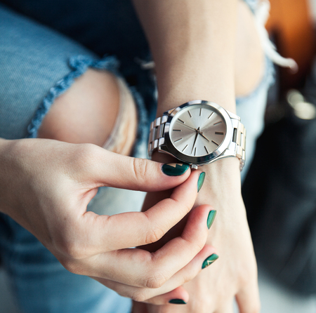 Stylish girl sitting in torn jeans and green modern manicure, bridge silver watch, bracelet. Fashion, lifestyle, beauty, apparel. Stock Photo