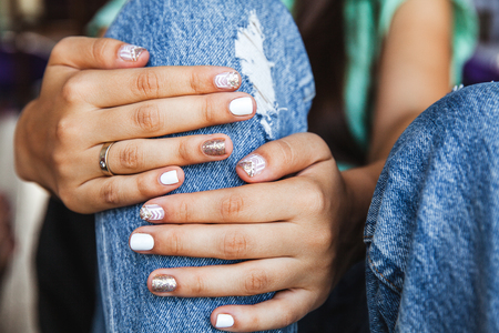 retro ripped jeans and a beautiful manicure on a background of a brick wall. Fashion style Stock Photo