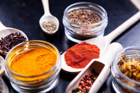 Spices on black background in special jars. Food Stock Photo