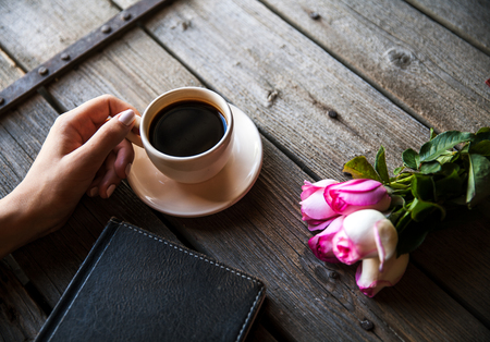 two page spread: Female hand with a cup of coffee, book and flowers on wooden background. Flowers, break, work Stock Photo