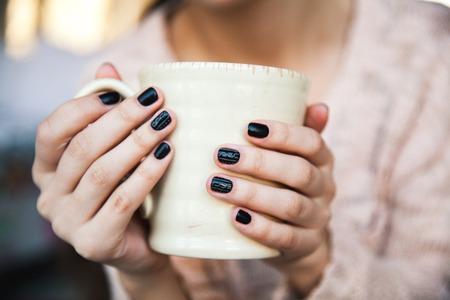 소녀 손을 아름 다운 검은 매니큐어와 커피 한 잔 들고. 크리스마스