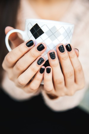 girl hands holding a cup of coffee with beautiful black manicure. Christmas