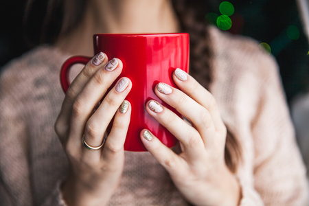 Womans hand holding a red cup of coffee. With a beautiful winter manicure. Drink, fashion, morning