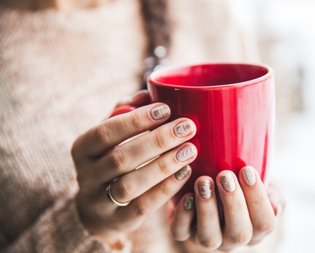 fall winter: Womans hand holding a red cup of coffee. With a beautiful winter manicure. Drink, fashion, morning