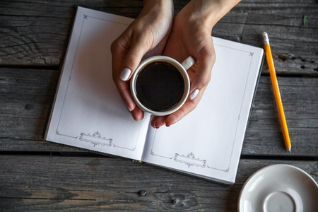 two page spread: Hands open Blank catalog, magazines,book mock up on wood table with coffee Stock Photo