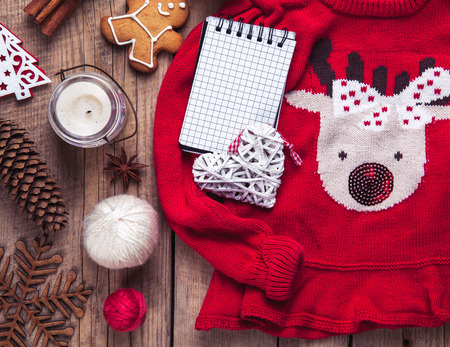 deer in heart: Christmas set. Warm blanket, sweater with a deer, candle, notebook, spices, cinnamon, pine cones, heart  on the wooden background