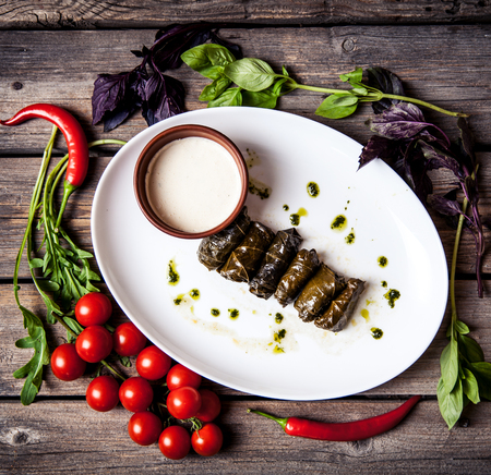 Cabbage rolls in grape leaves with sauce and tomatoes.