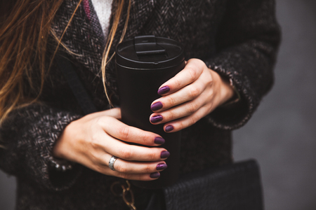 girl in stylish coat with beautiful manicure hand holding a black vacuum tumbler on a gray background a Stok Fotoğraf