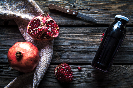 Pomegranate and bottles of essence or tincture on wooden rustic table a Imagens