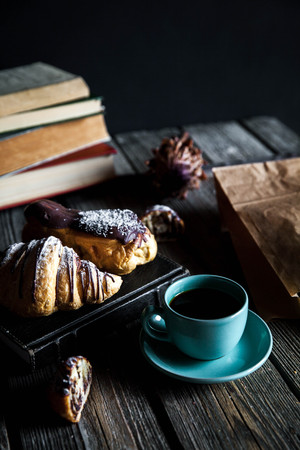 Croissant and white cup of black coffee on brown canvas. A Stock Photo