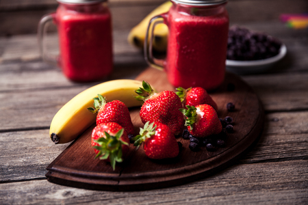 smoothie with banana and strawberry in the glass, fresh strawberries and bananas on the old wooden background a