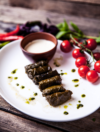 Cabbage rolls in grape leaves with sauce and tomatoes. Food a