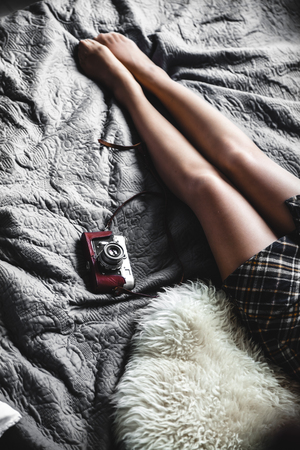 A girl rests in a gray bed with an old camera. Stock Photo
