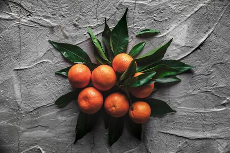 Tangerines (oranges, mandarins, clementines, citrus fruits) with leaves on gray cement background. Organic vegetarian food. Winter local fruits. Healthy detox eating concept. Copy space.