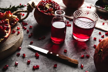 Red pomegranate juice in a glass, ripe and cut pomegranate and a sprig of mint on a gray concrete background. Vitamin, antioxidant and health food concept. Flat lay.Top view. a