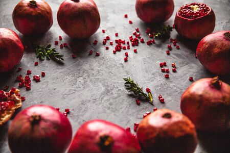 Pomegranate fruit. Ripe and juicy pomegranate on rustic grey background with copy space for your text.