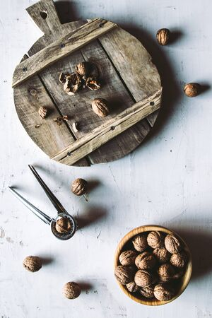 Walnuts in wooden bowl on table with Nutcracker.