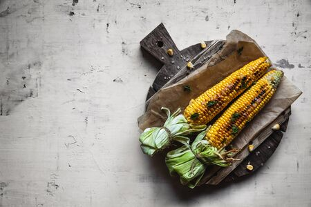 Grilled corn cobs with sauce, coriander on old shabby wooden white