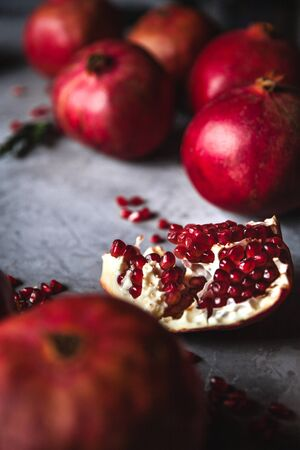 Pomegranate fruit. Ripe and juicy pomegranate on rustic grey  with copy space for your text. Stock Photo