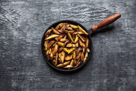 Fried hot potatoes in a pan, spices. Stockfoto