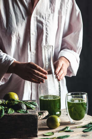 Woman pouring freshly blended green and white smoothie in glass jar with ingredients around on a rustic wooden table. Healthy eating and lifestyle concept. Detox diet. Recipe ideas. Banco de Imagens