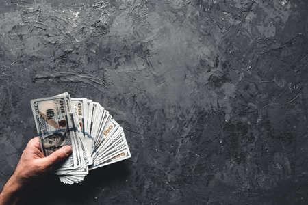 Hand holding money against dark background. Business concept, development perspective. Stock Photo