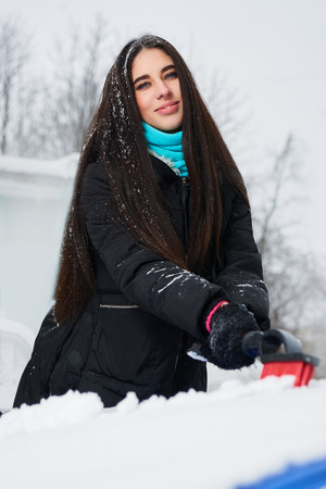 scrape: Beautiful young woman removing snow from her car Stock Photo