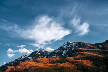 ridgeline: Mountain in the snow with orange trees and a blue sky