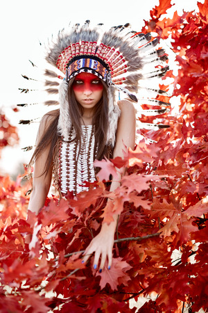 chieftain: Beautiful girl in a suit of the American Indian on the background of maple leaves