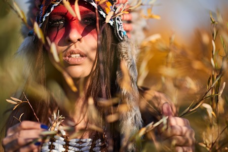 Beautiful girl in a suit of the American Indian. In Sunny day 写真素材