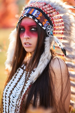 female shaman: Beautiful girl in a suit of the American Indian. In Sunny day Stock Photo