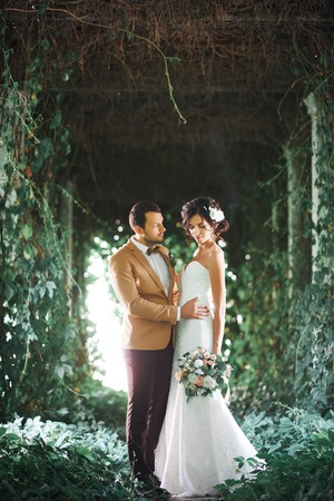 the moments: Young wedding couple enjoying romantic moments outside in arc