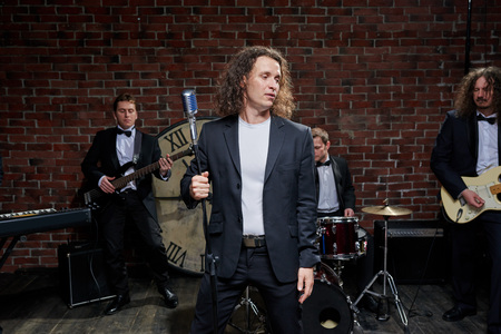 herman: Musicians playing the drums on brick wall background