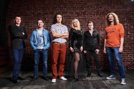 soloist: photo of music band in studio.Musicians and woman soloist posing over brick Stock Photo