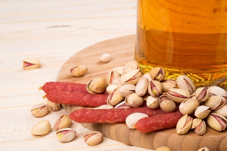 Smoked sausage with beer and pistachios Stock Photo