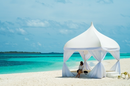 Girl in a tent on the shores of the azure ocean (Maldives - Lhaviyani Atoll)