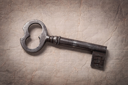 Old key on a crumpled paper
