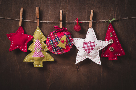 jobbing: Christmas tree ornaments on rope over rustic wooden board with copy space Stock Photo