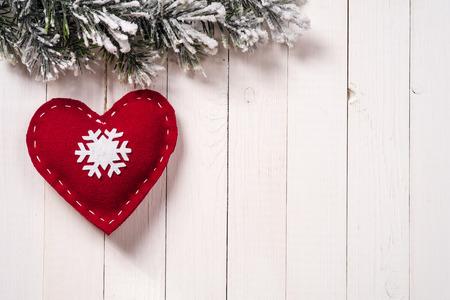 コピー スペースでの木材の背景にモミの枝とハートの形でのクリスマスの装飾