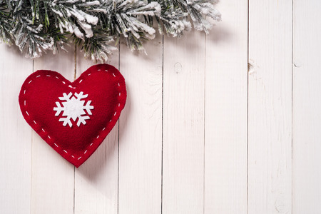 Christmas decoration in the form of heart with fir branches on wood background, with copy space